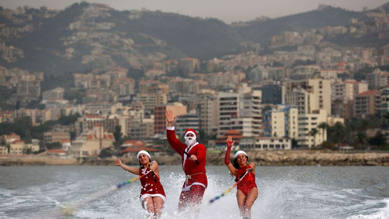 Members of a Lebanese water ski club perform while dressed in Santa Clause outfits in the bay of Jounieh