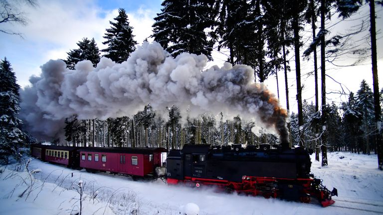 A steam powered locomotive of the Harz Narrow Gauge Railways travels through snow towards the station Brocken in Wernigerode, Germany
