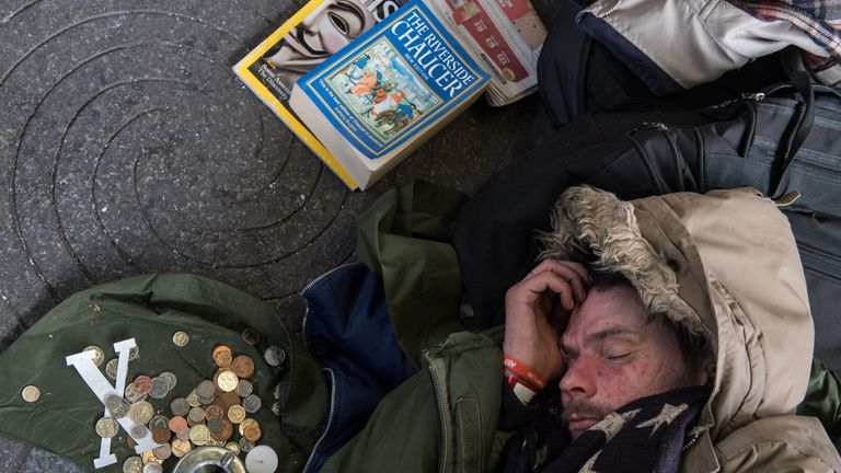 A homeless man sleeps next to donations from the public and his books outside Green Park underground station in London