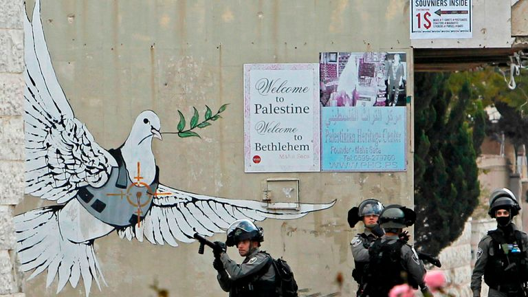 Israeli border guards hold a position next to a mural during clashes with Palestinian protesters following a demonstration in Bethlehem