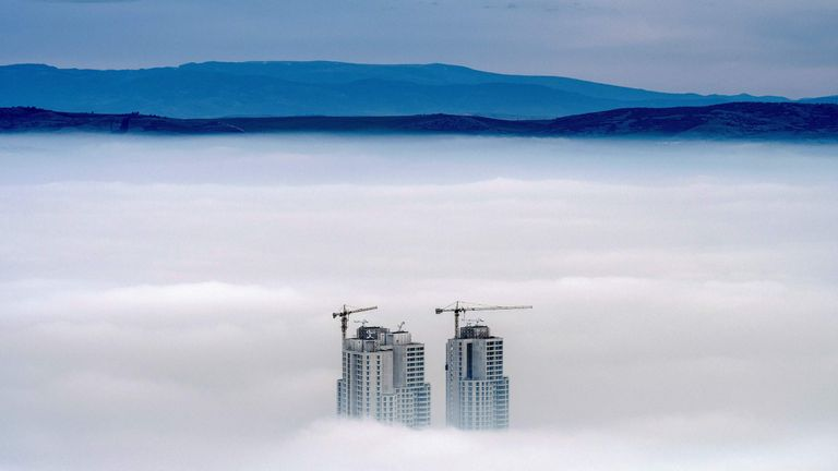 A view from Vodno Mountain shows the tops of the city's highest buildings above clouds in an area with a high level of air pollution in Skopje, Macedonia
