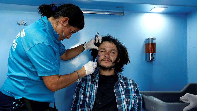 A volunteer shaves a homeless man in a bus equipped with showers, as part of Pro Mundo Foundation's project for people living on the streets, in San Jose, Costa Rica