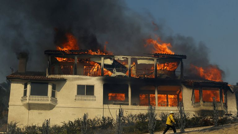 A firefighter inspects a burning home during a wind-driven wildfire in Ventura, California