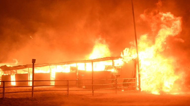 Wildfire engulfs horse stables in an early-morning Creek Fire that broke out in the Kagel Canyon area in the San Fernando Valley