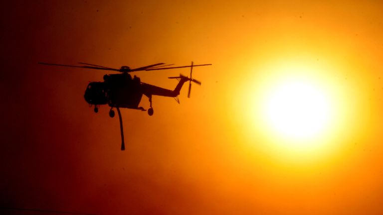 A firefighting helicopter passes by the smoke covered sun