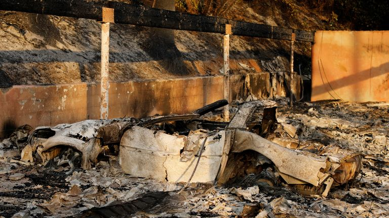 The burnt remains of an automobile at the Hawaiian Village apartments