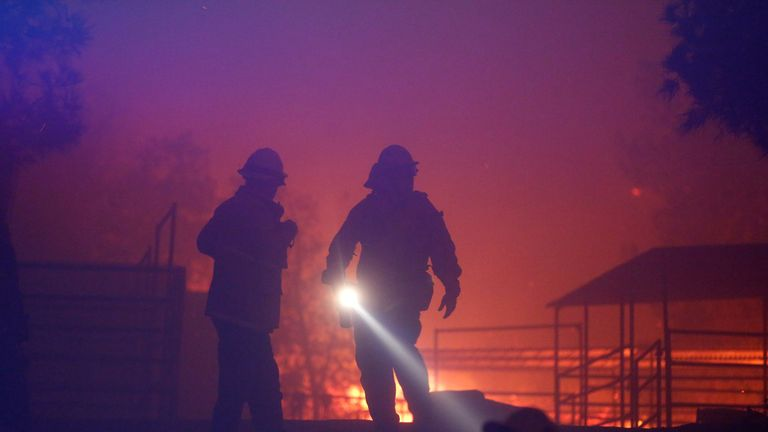 Firefighters walk through a horse ranch threatened by the Creek Fire