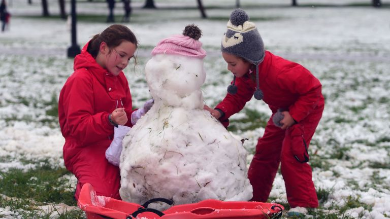 Two girls make a snowman on Primrose Hill in London