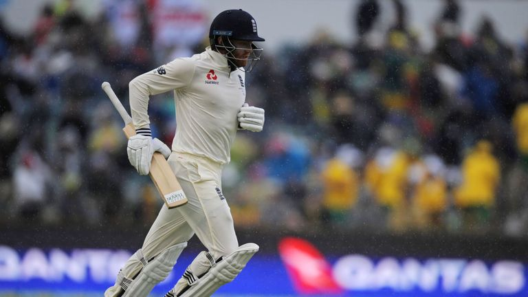 England's Jonny Bairstow runs off the field as rain halts play on day four of the third Ashes cricket Test match between England and Australia in Perth on
