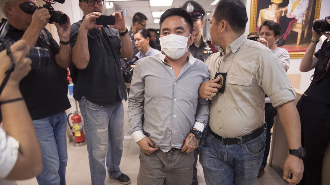 Boonchai Bach (C), 40, a Vietnamese national with Thai citizenship and alleged kingpin in Asia's illegal trade in endangered species, is escorted past journalists as he is processed at a police station in Bangkok on January 20, 2018