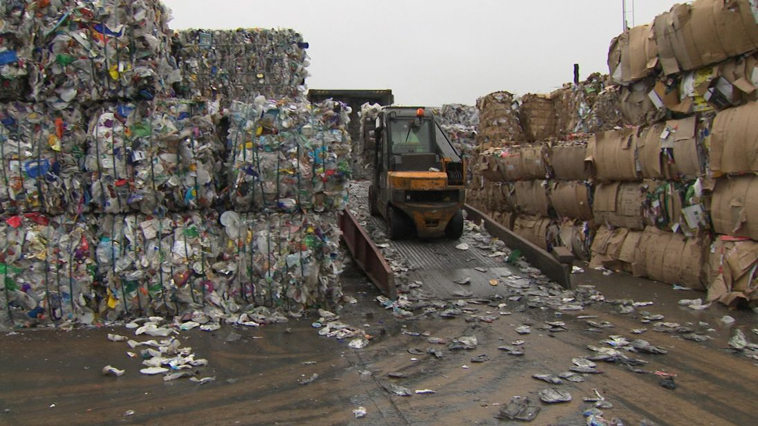 A truck loads bales of plastics recycling into a shipping container