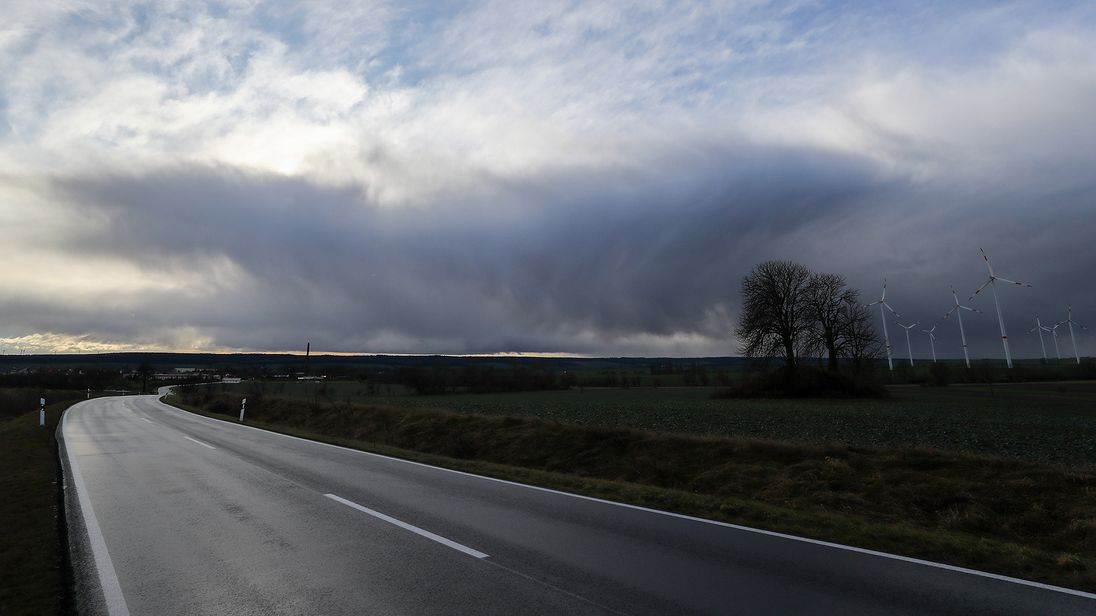"Clouds sweep over a  road and a field with wind turbines on January 3, 2018 near Bischofsroda, central Germany, as parts of the country are hit by a stormy depression named ""Burglind"". / AFP PHOTO / dpa / Jan Woitas / Germany OUT        (Photo credit should read JAN WOITAS/AFP/Getty Images)"
