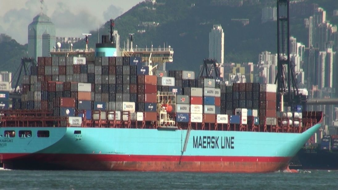 A shipping container transports goods through Hong Kong