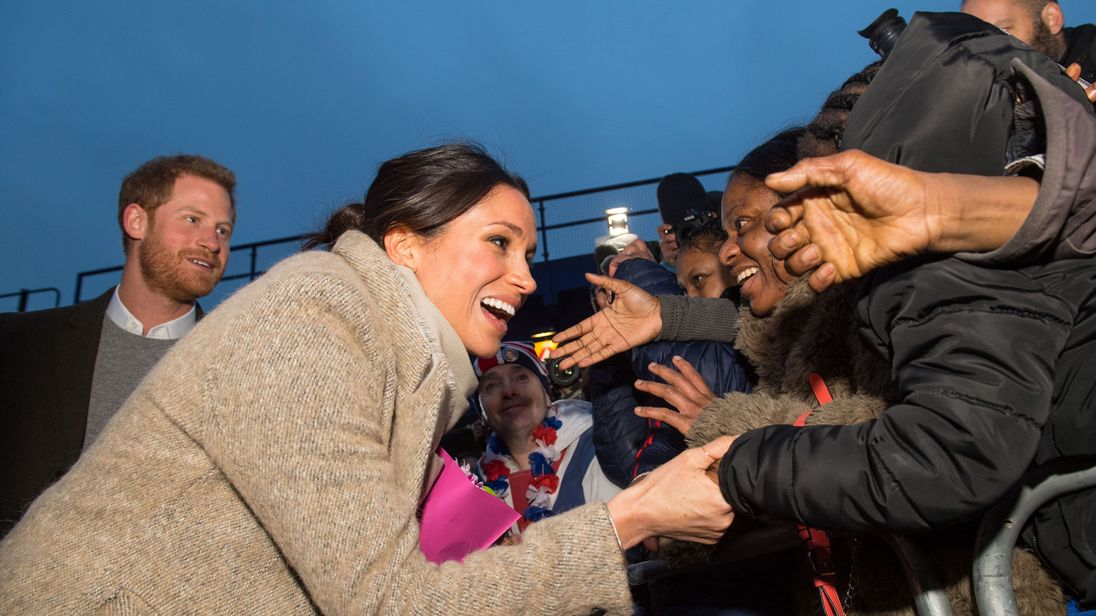 Britain's Prince Harry (L) and fiancée US actress Meghan Markle meet well-wishers as they leave after a visit to Reprezent 107.3FM community radio station in Brixton, south west London on January 9, 2018. During their visit to the station, they met some of the presenters, content producers and staff, heard more about their training programmes, and met some of the current and former volunteers who have benefitted from the training. / AFP PHOTO / POOL / Dominic Lipinski (Photo credit should read D