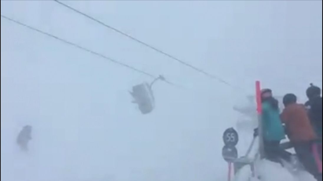 Skiers look on helpless as the lift pitches violently from side to side