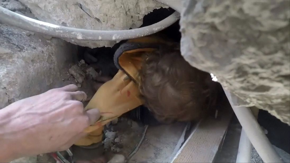 The child is pulled from the rubble