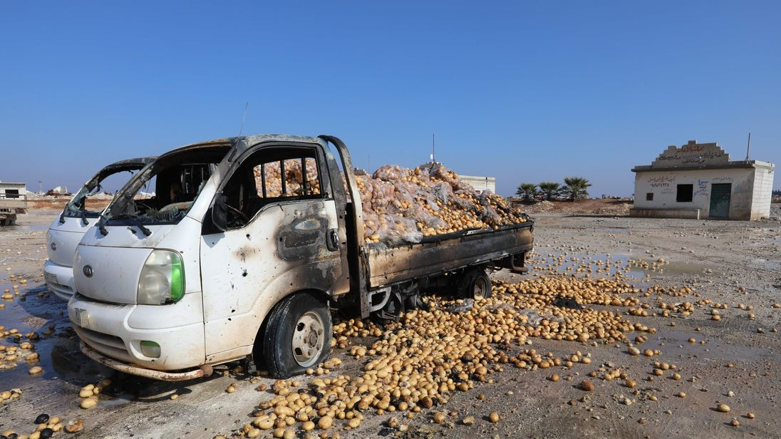 Small trucks loaded with potatoes stand abandoned after airstrikes in Saraqeb