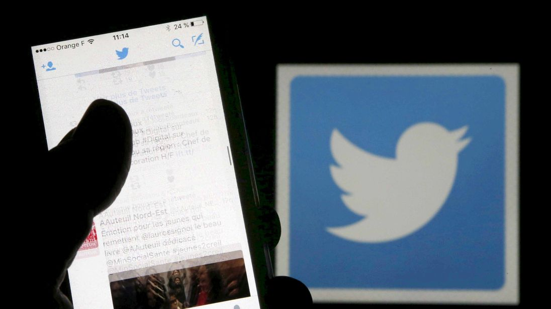 A man reads tweets on his phone in front of a displayed Twitter logo