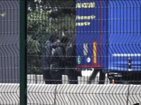 A group of teenagers huddle around the back of a lorry and get in
