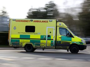 An East of England Ambulance is driven along the road in Cambridge.