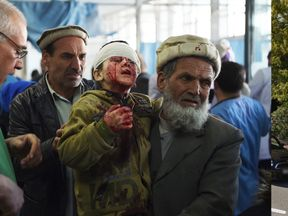 An Afghan man holds a wounded child, after a car bomb exploded near the old Interior Ministry building, at Jamhuriat Hospital in Kabul on January 27, 2018