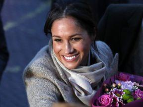 Meghan Markle receives a bouquet of flowers from a fan in Brixton
