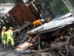 Emergency personnel prepare to rescue a trapped woman inside a collapsed house in Montecito, California, U.S. January 9, 2018. Pic: Santa Barbara News-Press