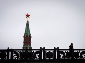 TOPSHOT - A man walks on a bridge past the Kremlin's Spasskaya (Saviour) Tower in central Moscow on January 3, 2018. Russia celebrates the Orthodox Christmas on January 7. / AFP PHOTO / Yuri KADOBNOV (Photo credit should read YURI KADOBNOV/AFP/Getty Images)