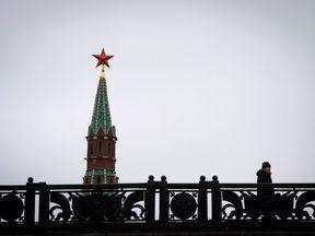 TOPSHOT - A man walks on a bridge past the Kremlin's Spasskaya (Saviour) Tower in central Moscow on January 3, 2018. Russia celebrates the Orthodox Christmas on January 7. / AFP PHOTO / Yuri KADOBNOV (Photo credit should read YURI KADOBNOV/AFP/Getty Images)
