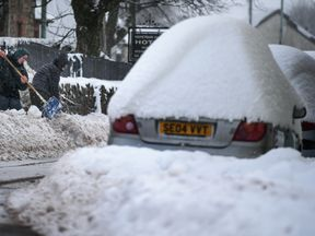 Locals try to clear snow from the front of their homes as parked cars sit covered in the white stuff in Dumfries, Scotland