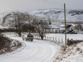 A car navigates a snowy road in Longdon Beck as the area in the North Pennines was blanketed by snow overnight