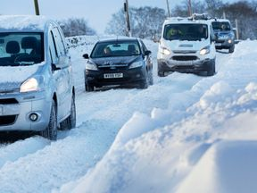 Vehicles make their way through heavy snow in Midlothian near Edinburgh