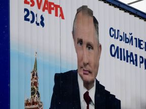 A rotating billboard shows an image of Russia's President Vladimir Putin and lettering '18 March 2018' in Moscow on January 15, 2018