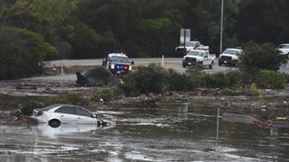 An abadoned car floats in flooded waters and debris on the freeway after a mudslide in Montecito, California