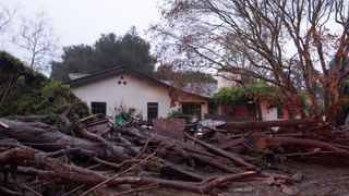 A house surrounded by flooded water and debris after a mudslide in Montecito, California,