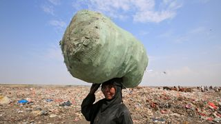 A woman carries a sack of recyclables she collected from a garbage dump on the outskirts of the Red Sea port city of Hodeida, Yemen