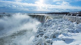 Visitors take pictures near the brink of the ice covered Horseshoe Falls in Niagara Falls, Ontario, Canada
