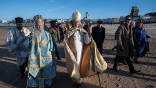 The Archbishop of Thyateira and Great Britain, and the Bishop of Dover, walk along Margate beach after a Greek Orthodox blessing