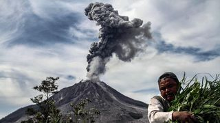 A man carries his harvest from his vegetable field, as Mount Sinabung spews thick smoke, in Karo, North Sumatra