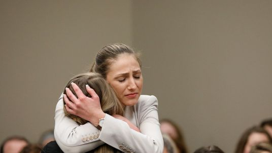 One of Nassar's victims is hugged after giving a statement in court