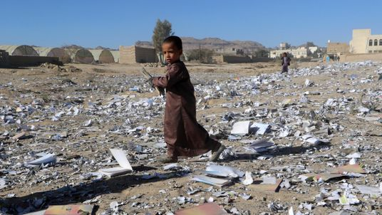 A boy holds a book as he walks on books scattered on the ground after an air strike hit a school book storage building in the northwestern city of Saada, Yemen