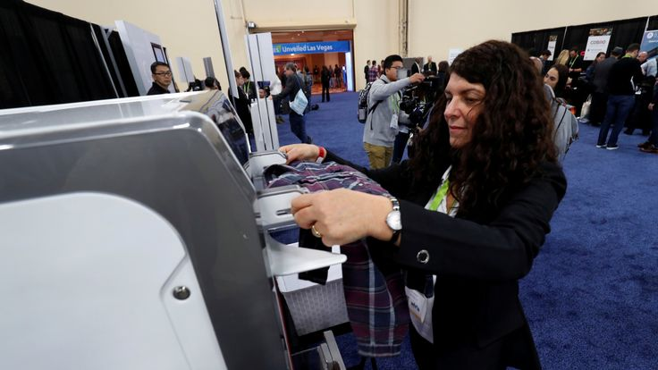 Debbie Cohen-Abravanel, CMO at FoldiMate, feeds laundry into a FoldiMate automatic laundry folding machine
