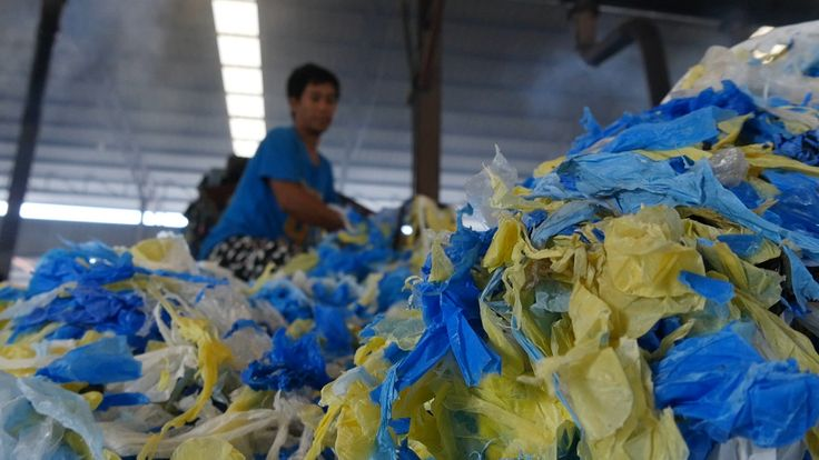A worker in Thailand processes plastics recycling