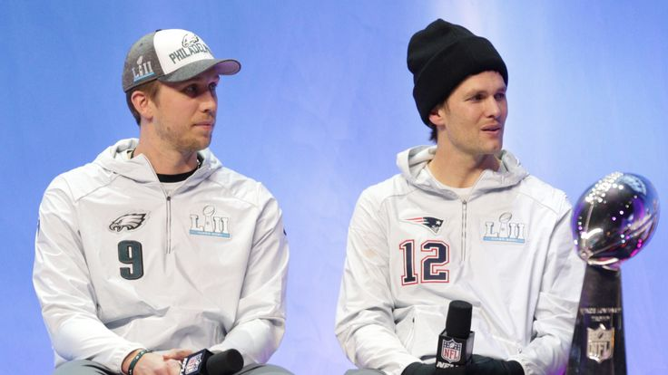 Philadelphia Eagles quarterback Nick Foles (9) and New England Patriots quarterback Tom Brady (12) sit on stage with the Vince Lombardi Trophy during Super Bowl LII Opening Night