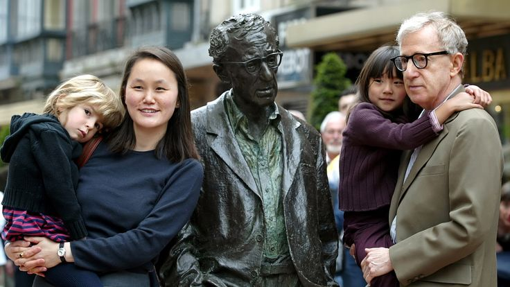 Woody Allen holds his daughter Manzie Tio as his wife Soon-Yi Previn carries daughter Bechet while they pose near a statue of Allen in Oviedo, northern Spain