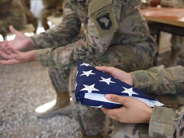 A US soldier holds the national flag ahead of a handover in Lashkar Gah