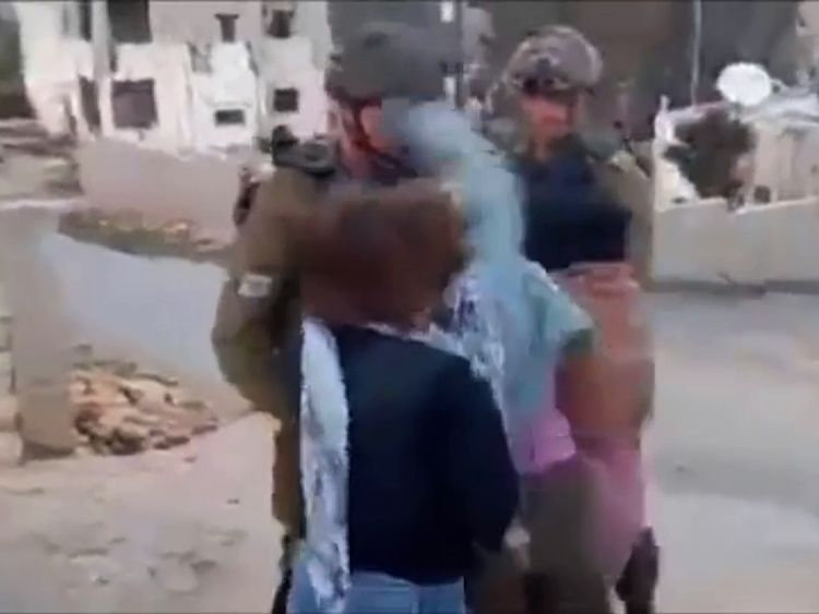 She appears to hit a second soldier in the face in the video