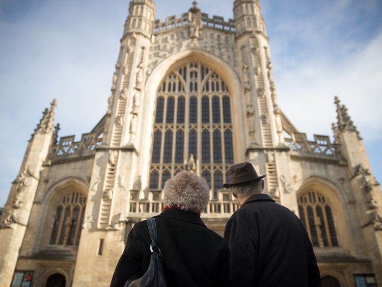 Visitors admire the west front of the Bath Abbey