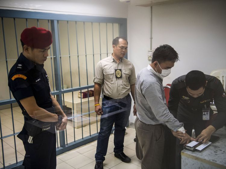 Boonchai Bach (2nd R), 40, a Vietnamese national with Thai citizenship and alleged kingpin in Asia's illegal trade in endangered species, is fingerprinted by Thai police in Bangkok after his arrest on January 20, 2018. Thai police have arrested an alleged kingpin in Asia's illegal trade in endangered species, dealing a blow to family-run syndicate that smuggles elephant ivory, rhino horn and tiger parts to Chinese and Vietnamese dealers. / AFP PHOTO / Robe