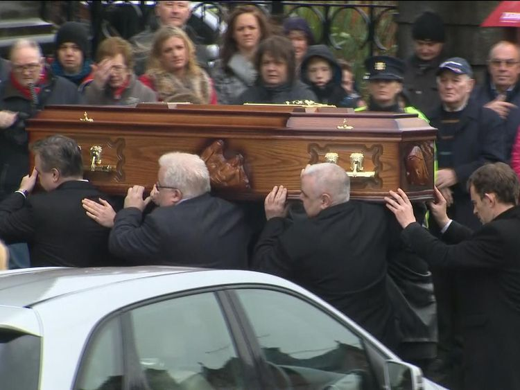 The coffin being carried as mourners watch on